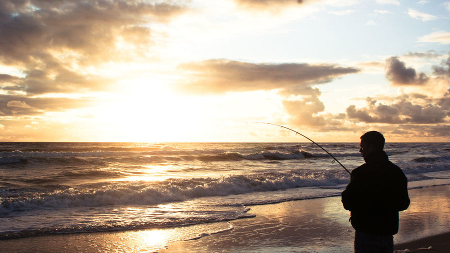 Silhouette man fishing on shore during sunset