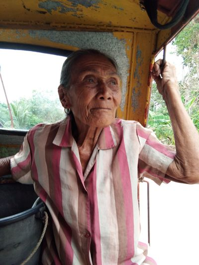 Senior woman sitting in land vehicle