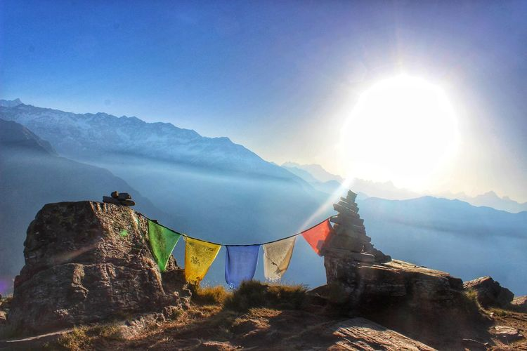 Prayer flags on mountains against bright sun