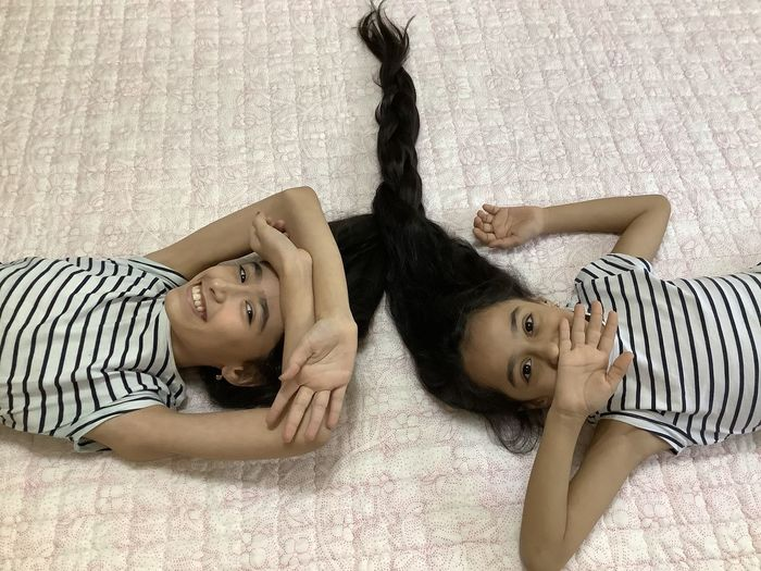 High angle portrait of girls relaxing on bed at home