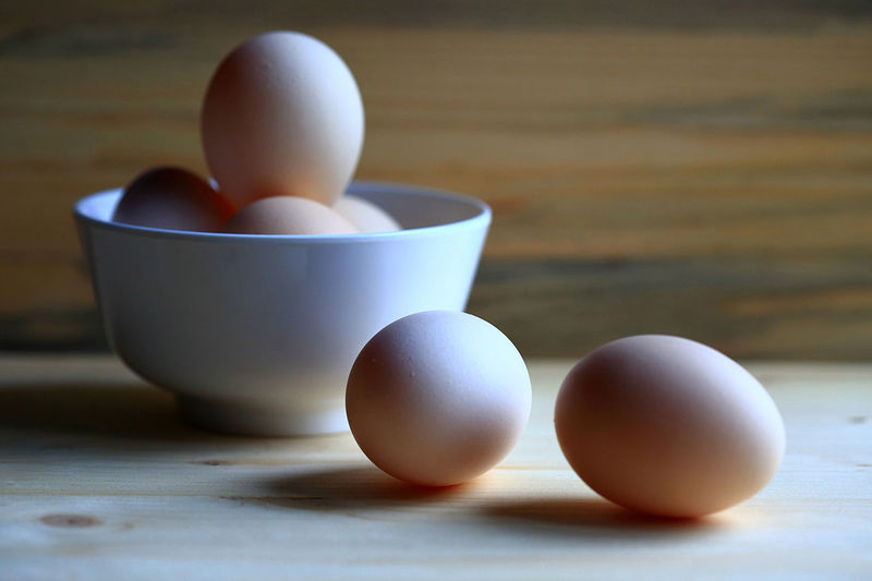 Eggs in bowl and on table with brown background. Bowl Brown Close-up Day Egg Egg Carton Eggcup EyeEm Food Fragility Freshness Health Healthy Eating Healthy Lifestyle Indoors  Me Meal No People Nutrition Oval Shape Still Life StillLifePhotography Table Water
