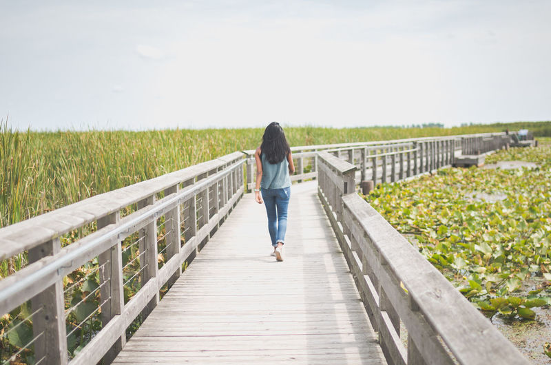 Rear View Of Woman Walking On Walkway