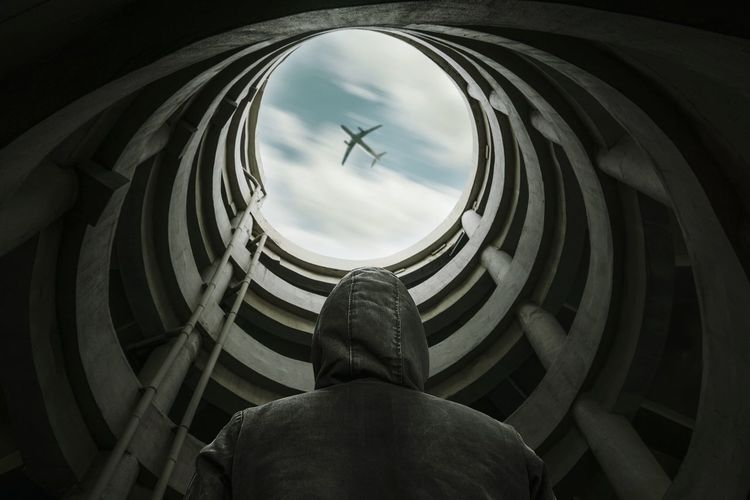 Low Angle View Of Man Standing In Building Against Airplane