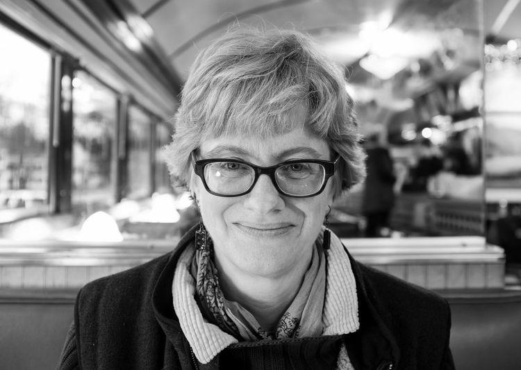 Portrait Of Smiling Woman Wearing Eyeglasses At Restaurant