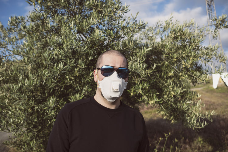 Portrait of man standing wearing mask standing by tree