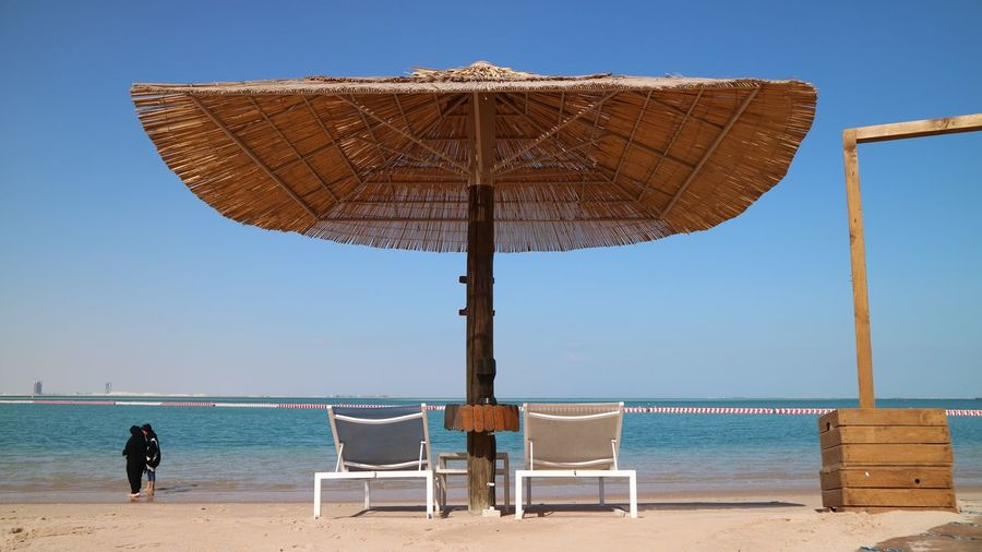 Sea beach in Pearl Qatar Doha Qatar Days Arabic Beach Beauty In Nature Chair Clear Sky Holiday Horizon Horizon Over Water Land Nature Outdoors Parasol Protection Qatar Qatarlife Sea Sky Summer Sunshade Trip Umbrella Vacations Water