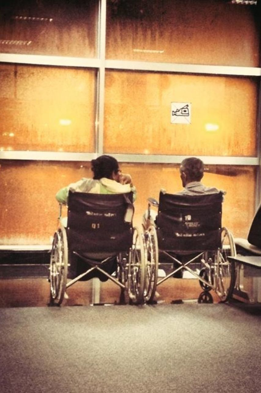 rear view, indoors, two people, full length, real people, men, sitting, wheelchair, illuminated, physical impairment, women, day, people