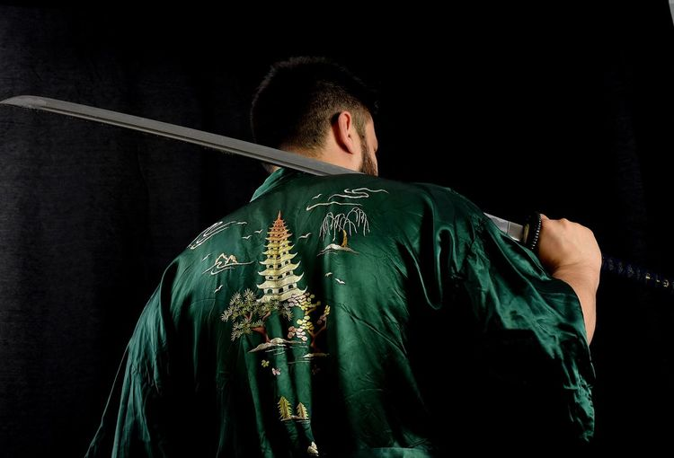 Rear View Of Man Holding Sword Against Black Background
