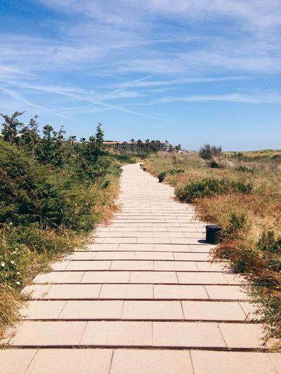 Footpath leading towards landscape against sky
