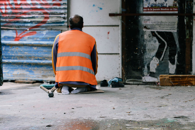 Rear View Real People People Men Occupation Day Street Clothing Full Length City Orange Color Architecture Lifestyles Outdoors Working Footpath Built Structure Sitting Social Issues