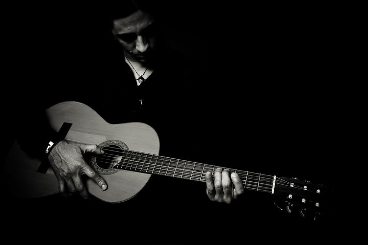 Close-up of man holding guitar over black background