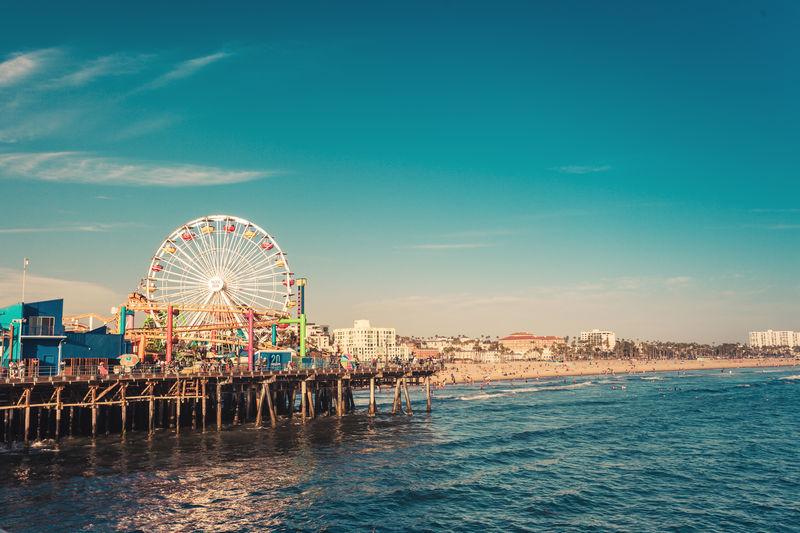Ferris wheel by sea against blue sky