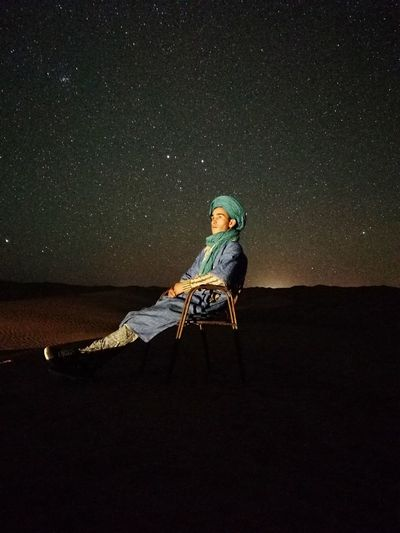 Man sitting on chair against star field