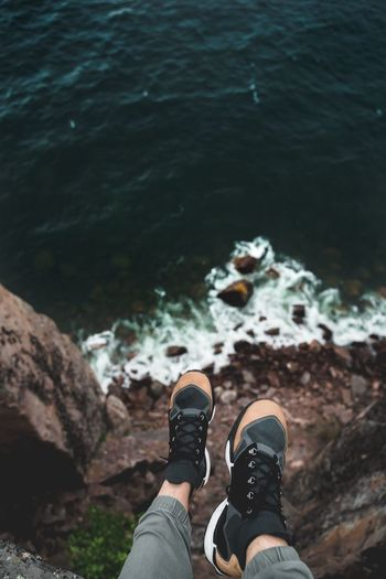 Low section of man on cliff over sea