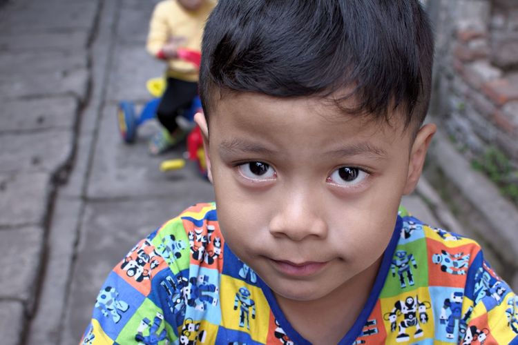 Hmmm what's in there ?... Bandung Shooter Indonesian Shooter Boys Casual Clothing Child Childhood Close-up Contemplation Focus On Foreground Front View Headshot Human Face Innocence Leisure Activity Lifestyles Looking At Camera Males  Men One Person Outdoors Portrait Real People