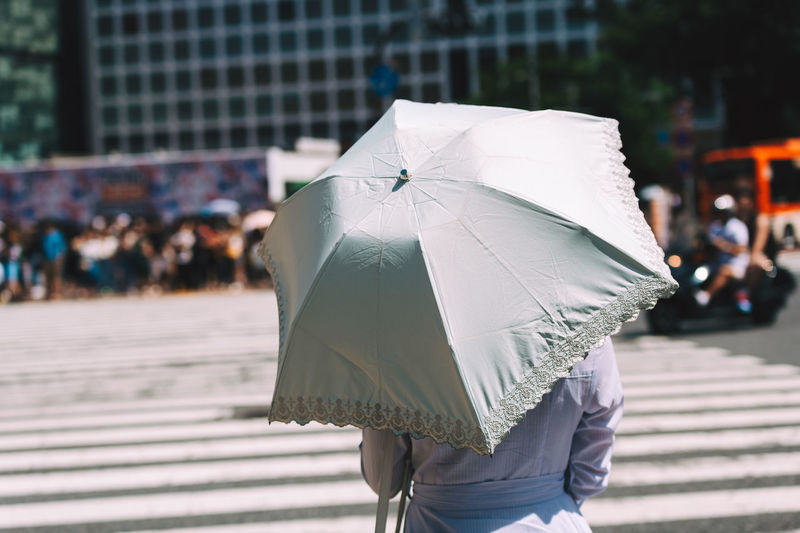 Midsection of woman with umbrella walking on street during rainy season