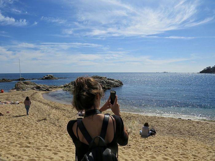 Rear View Of Woman Photographing Through Mobile Phone At Beach