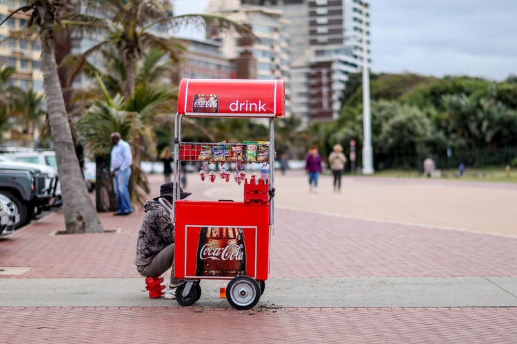 Durban beachfront Autumn Beach Candy Cart Coke Durban Durban Beachfront East Coast End Of Summer Food Truck Outdoors Palm Trees Red Refreshment Cart Refreshments Sand Selling On The Street South Africa Stationary Street Cart Sweet Vendor