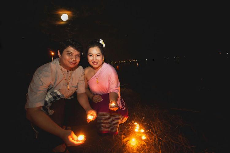 Portrait of couple holding lit tea lights at night