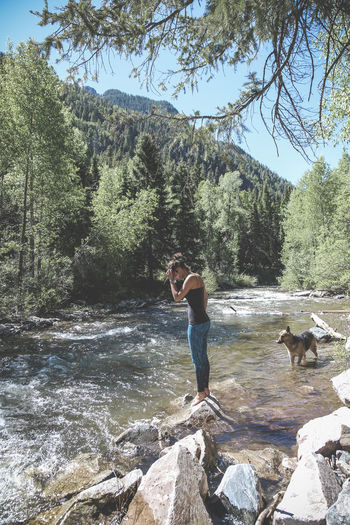 Woman With Dog Standing On Rock At Forest