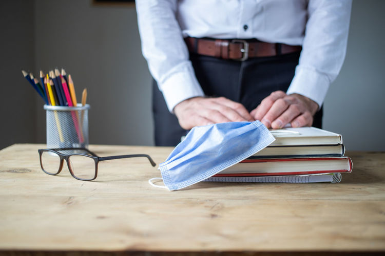 Midsection of man working with book on table