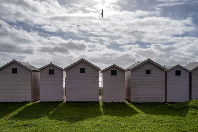 Beach huts on grass against cloudy sky