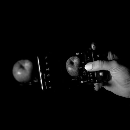 Close-up of hand holding camera over black background