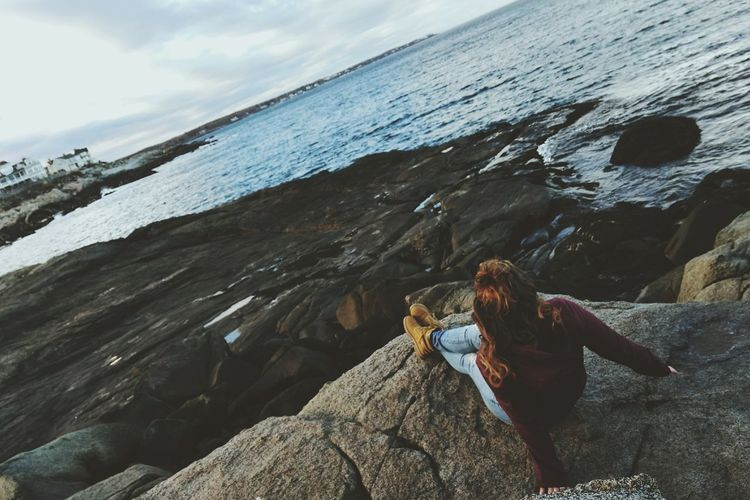 High angle view of young woman sitting on rock at beach