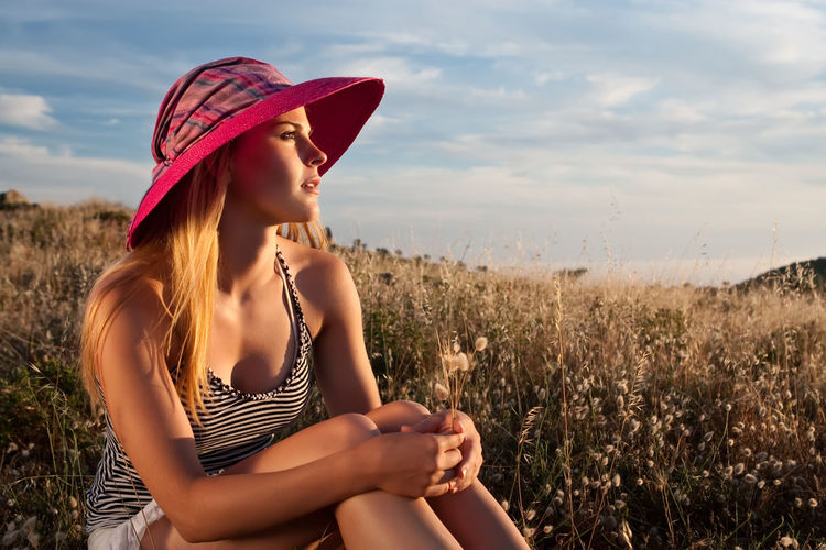 Young woman wearing hat sitting on grassy field against sky