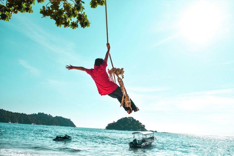 Boy on rope swing against sky