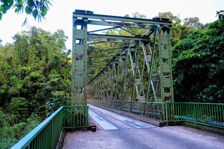 Bridge over empty road against sky