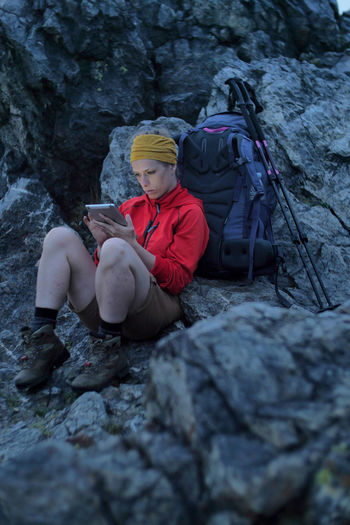 caucasian female hiker using portable tablet technology outdoors on a alpine hiking trail Alpine Backpacking Camping Expedition Freedom Hiking Tablet Travel Trekking Woman Youth Activity Adventure Battery Clothing Communication Connection Female Full Length Hobby Holding Internet Leisure Activity Lifestyles Nature Navigation One Person Outdoors People Portable Information Device Real People Rock Rock - Object Sitting Solid Technology Trail Wireless Technology