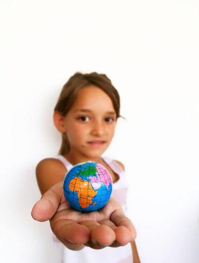 Portrait of girl holding globe against white background