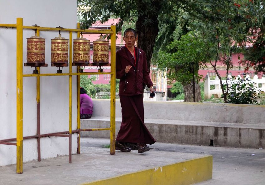 Bhutan Thimphu Buddhist Monk Adult Bhutan Bhutanese Bhutanese Culture Buddism Day Front View Full Length Happiness Lifestyles Looking At Camera Mature Adult One Person Outdoors People Portrait Praying Wheels Real People Smiling Standing Tree Young Adult Young Women