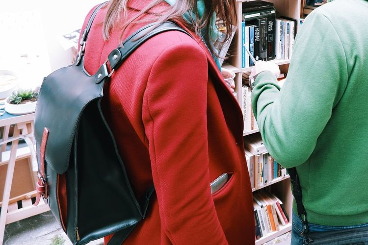 Rear view of man and woman standing on book