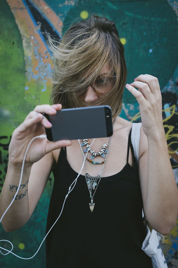 Woman taking selfie from mobile phone with tousled hair against wall