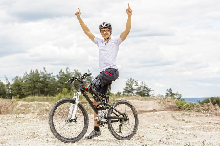 Disabled man riding bicycle on dirt road against sky