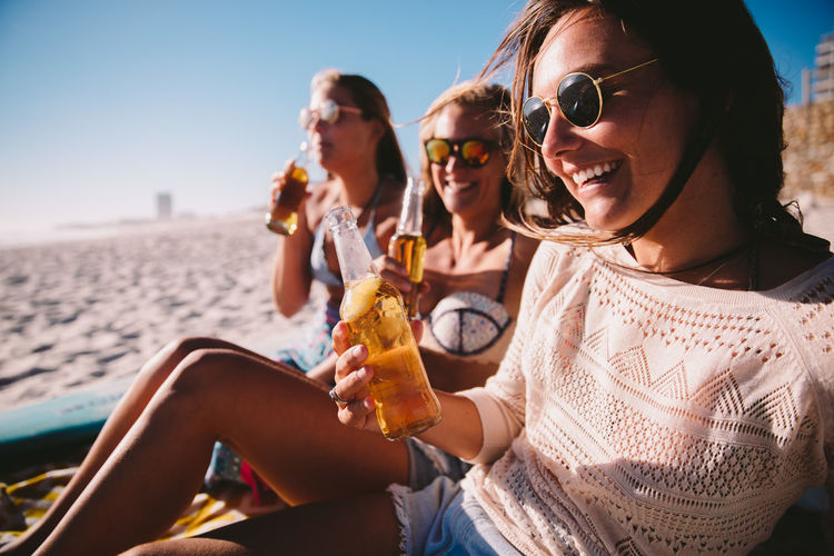 Sunglasses Women Leisure Activity Fashion Young Women Sitting Young Adult Sky Smiling Adult Friendship Beer Focus On Foreground Happiness Beach Lifestyles Sunlight Togetherness Outdoors Drinking