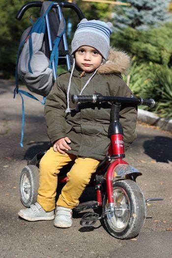Portrait Of Cute Boy Sitting On Tricycle On Footpath
