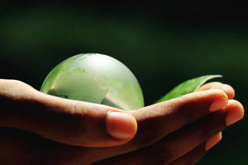Close-up of human hand holding globe and leaf against black background