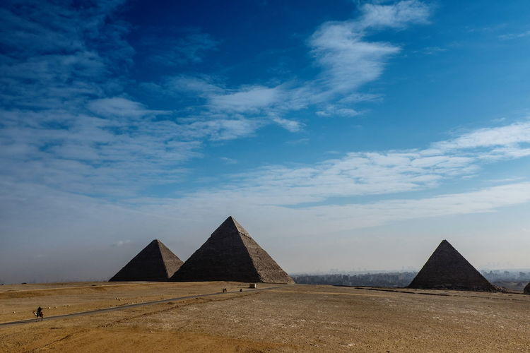 Pyramids against cloudy blue sky
