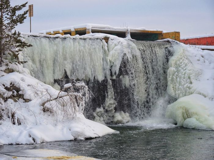 Scenic view of waterfall against sky during winter
