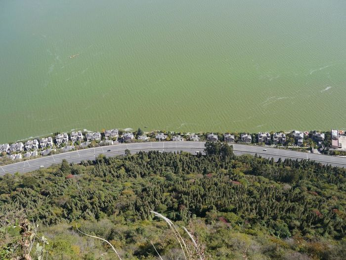 High Angle View Of Road By Sea Against Buildings