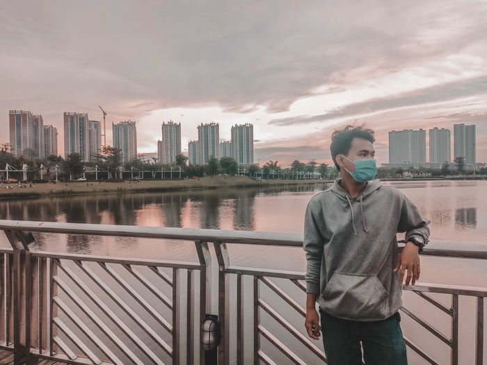 Man standing by railing and cityscape against sky