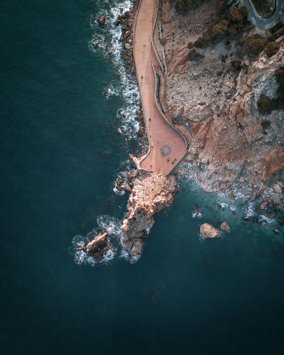 High angle view of rock formation and walkway by the beach