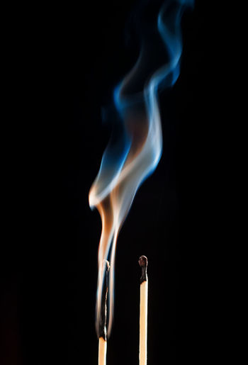 Close-Up Of Smoking Matchstick On Black Background