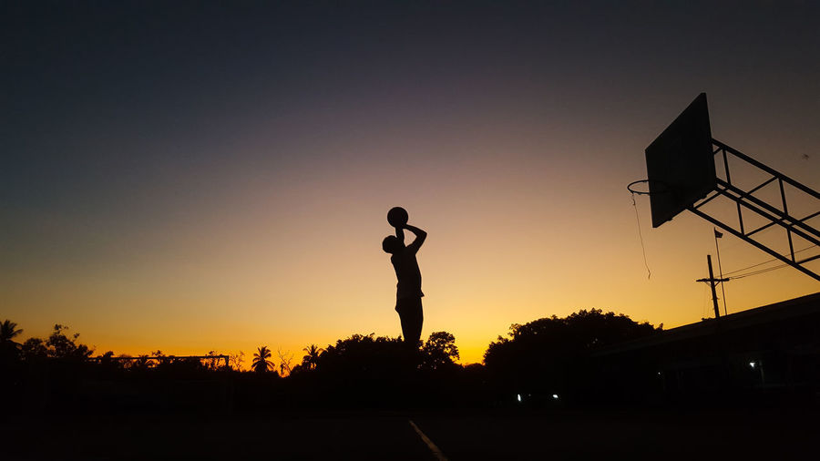 Silhouette man playing soccer against sky during sunset