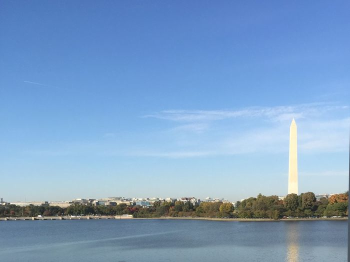 Washington monument by lake against blue sky