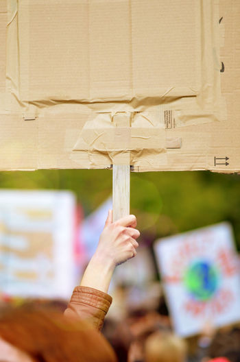 Cropped hand of woman holding placard during protest in city