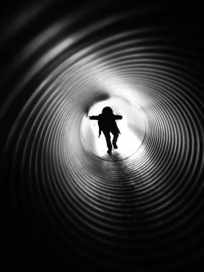 Silhouette boy walking in slide